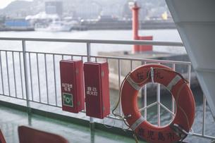 雄大な桜島を背景に錦江湾の鹿児島港と桜島港フェリーターミナルを結ぶ桜島フェリーの写真素材 [FYI04859861]