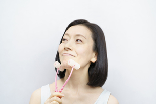 小顔マッサージをする中年女性の写真素材 [FYI04859896]