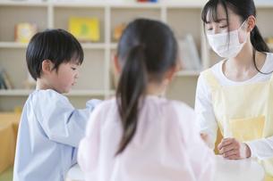 教室で遊ぶ子供と保育士の写真素材 [FYI04860266]