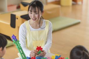 ブロックで遊ぶ子供と保育士の写真素材 [FYI04860267]
