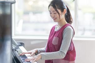 ピアノを弾く保育士の写真素材 [FYI04860268]