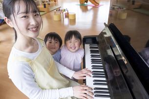 ピアノを弾く保育士と歌う園児の写真素材 [FYI04860272]