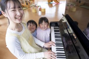 ピアノを弾く保育士と歌う園児の写真素材 [FYI04860273]