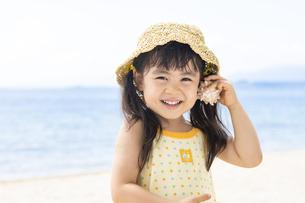 貝殻を耳に当てる女の子の写真素材 [FYI04860442]