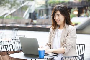 外でパソコンを開いて仕事をしている女性の写真素材 [FYI04860557]
