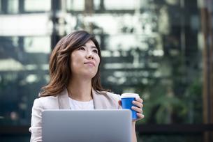 外でパソコンを開いてコーヒーカップを持っている女性の写真素材 [FYI04860584]