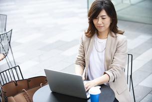 外でパソコンを開いて仕事をしている女性の写真素材 [FYI04860595]