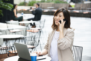 外でパソコンを開いて電話をしている女性の写真素材 [FYI04860602]