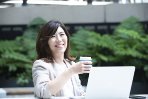 外でコーヒーを持って笑っている女性の写真素材 [FYI04860623]