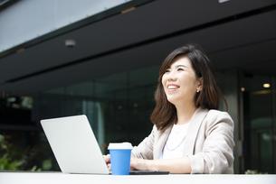 外でパソコンを開いて仕事をしている女性の写真素材 [FYI04860648]