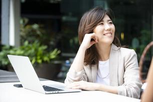 外でパソコンを開いて笑っている女性の写真素材 [FYI04860666]