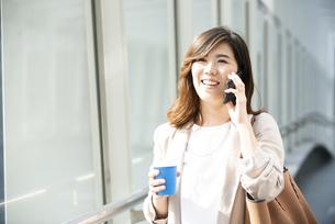 電話をしながら歩いている笑顔の女性の写真素材 [FYI04860671]