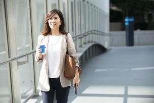 コーヒーとスマホを持って歩いている笑顔の女性の写真素材 [FYI04860681]