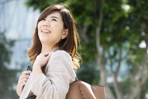 ビルの前でスマホを持って笑っている女性の写真素材 [FYI04860766]
