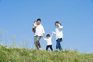 青空のもと、笑顔ではしゃぐ親子4人の写真素材 [FYI04860818]