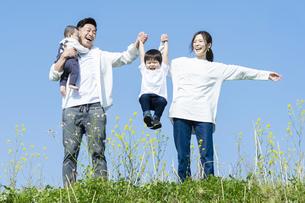 青空のもと、笑顔ではしゃぐ親子4人の写真素材 [FYI04860821]
