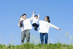 青空のもと、笑顔ではしゃぐ親子4人の写真素材 [FYI04860825]