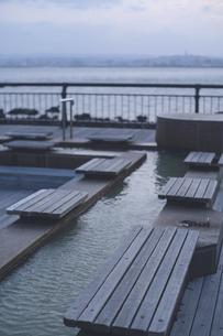 夕暮れの桜島 - 海を眺める溶岩なぎさ公園の足湯の写真素材 [FYI04860984]