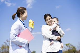 白衣を着てパペット人形を持つ女性と話す親子の写真素材 [FYI04860988]