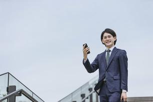 IoTのイメージ 通勤先から家の家電を操作する男性の写真素材 [FYI04861282]