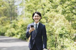 通勤中にスマートフォンを使用するビジネスマン・IoTイメージの写真素材 [FYI04861287]
