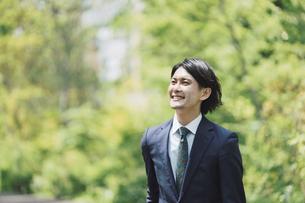 通勤中のビジネスマン・新緑の中の男性のビジネスシーンの写真素材 [FYI04861295]