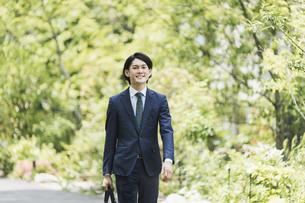 通勤中のビジネスマン・新緑の中の男性のビジネスシーンの写真素材 [FYI04861305]