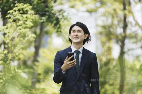 通勤中にスマートフォンを使用するビジネスマン・IoTイメージの写真素材 [FYI04861313]