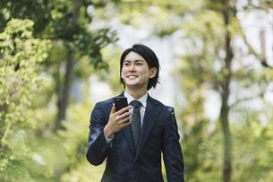 通勤中にスマートフォンを使用するビジネスマン・IoTイメージの写真素材 [FYI04861314]