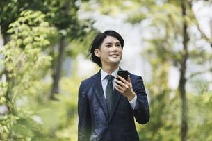 通勤中にスマートフォンを使用するビジネスマン・IoTイメージの写真素材 [FYI04861315]