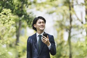 通勤中にスマートフォンを使用するビジネスマン・IoTイメージの写真素材 [FYI04861316]