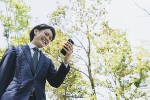 通勤中にスマートフォンを使用するビジネスマン・IoTイメージの写真素材 [FYI04861319]