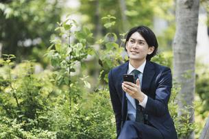 座ってスマートフォンを操作する男性・ビジネスシーン・ビジネスイメージの写真素材 [FYI04861326]