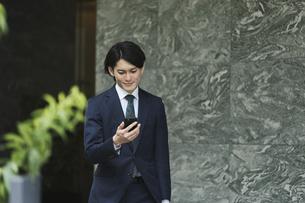 通勤中にスマートフォンを使用するビジネスマン・IoTイメージの写真素材 [FYI04861353]