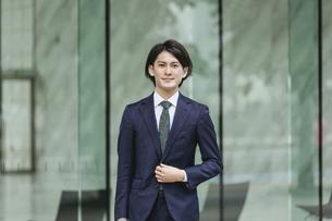 出社する若い男性・マンションのロビー背景・ビジネスイメージの写真素材 [FYI04861386]