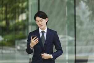 出社する若い男性・スマートフォンでIoT・ビジネスイメージの写真素材 [FYI04861393]