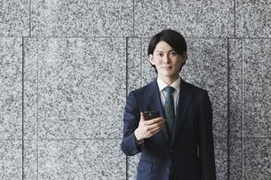 スマートフォンを持つ若い男性・IoTとビジネスのイメージの写真素材 [FYI04861416]
