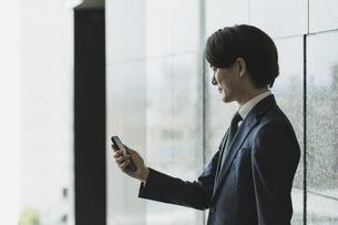 スマートフォンを持つ若い男性・IoTとビジネスのイメージ(逆光・横顔・シルエット)の写真素材 [FYI04861420]
