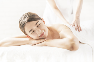 明るい雰囲気のエステサロンでマッサージを受ける若い女性の写真素材 [FYI04862200]