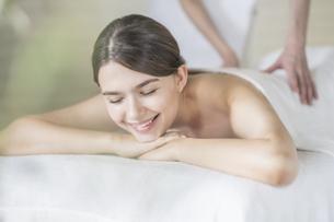 明るい雰囲気のエステサロンでマッサージを受ける若い女性の写真素材 [FYI04862202]
