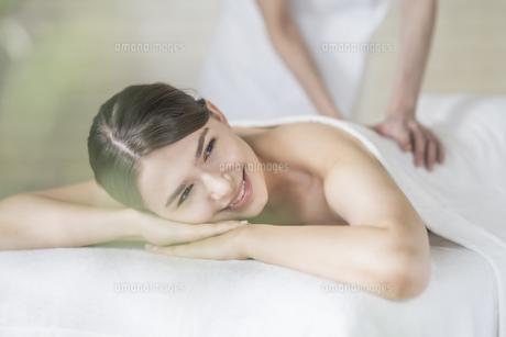 明るい雰囲気のエステサロンでマッサージを受ける若い女性の写真素材 [FYI04862203]