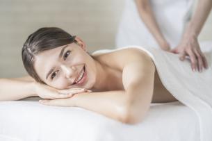 明るい雰囲気のエステサロンでマッサージを受ける若い女性の写真素材 [FYI04862204]