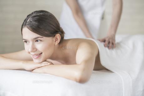 明るい雰囲気のエステサロンでマッサージを受ける若い女性の写真素材 [FYI04862205]