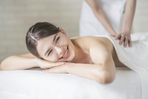 明るい雰囲気のエステサロンでマッサージを受ける若い女性の写真素材 [FYI04862207]