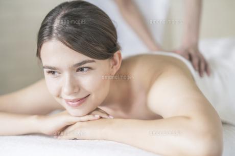明るい雰囲気のエステサロンでマッサージを受ける若い女性の写真素材 [FYI04862208]