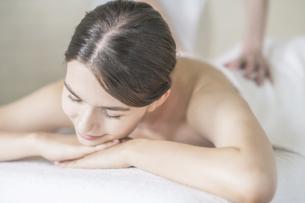 明るい雰囲気のエステサロンでマッサージを受ける若い女性の写真素材 [FYI04862209]