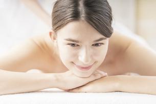 明るい雰囲気のエステサロンでマッサージを受ける若い女性の写真素材 [FYI04862210]