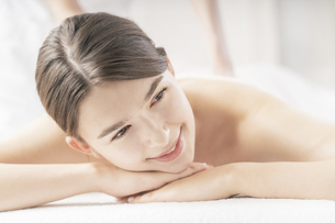明るい雰囲気のエステサロンでマッサージを受ける若い女性の写真素材 [FYI04862211]