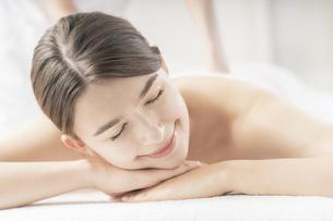 明るい雰囲気のエステサロンでマッサージを受ける若い女性の写真素材 [FYI04862212]