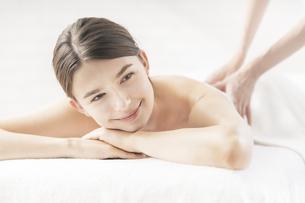 明るい雰囲気のエステサロンでマッサージを受ける若い女性の写真素材 [FYI04862215]